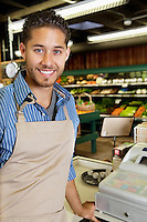 Portrait of handsome store employee standing near cash register in supermarket