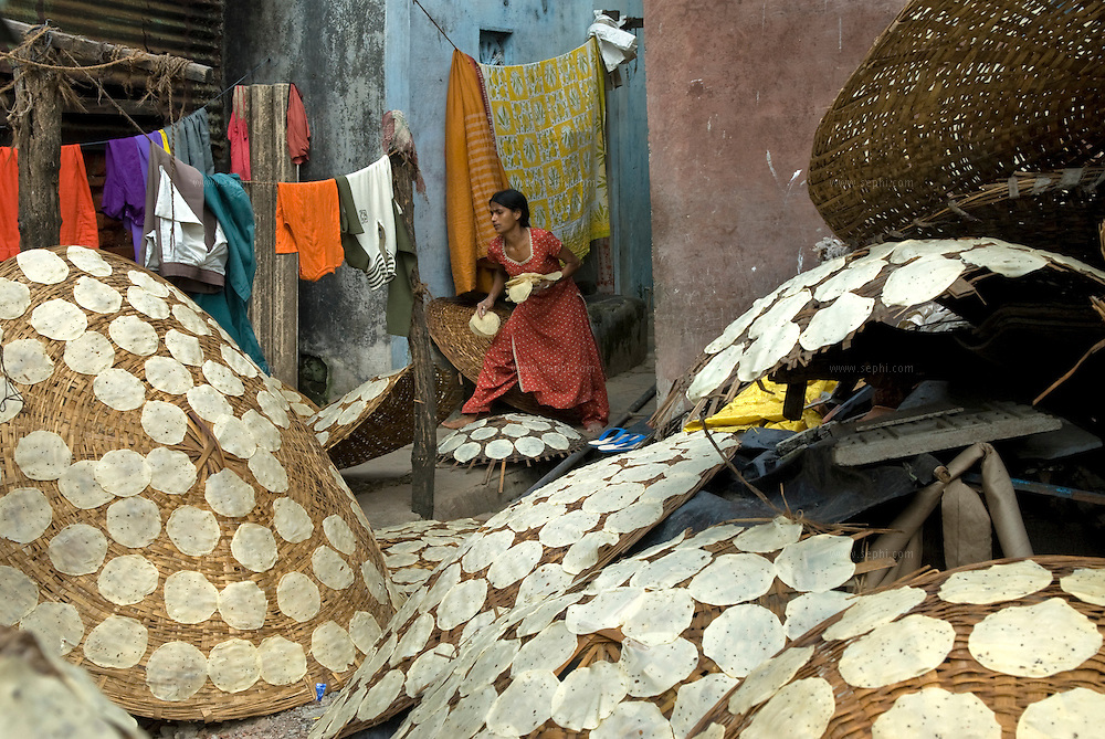A woman puts home made papad to dry in the sun. Making papads is a common occupation for women. The girls help with the work when they come home from school.