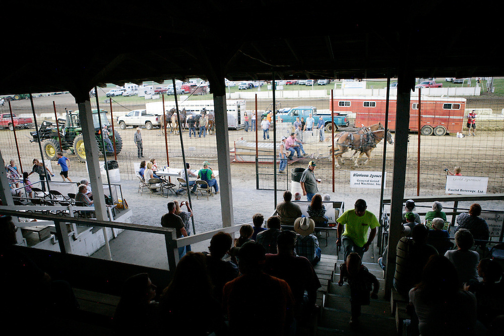 Spectators watch a horse pulling competition at the Mercer County Fair in Aledo, IL on Thursday, July 14.  Spectators can buy into teams of horses to win a portion of their contest earnings.
