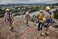 A 14 member crew of LA Fire Department's station 88 Urban Rescue and Search Team remove graffiti tags off of L.A.'s Eagle Rock. Crew members harnessed by ropes repelled down the face of the iconic Eagle Rock and grind away at graffiti tags. The work was deemed too dangerous for regular removal teams to attempt.