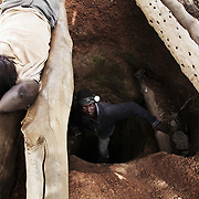 A man is relaxing next to a whole leading into a gold mine, another coming out back into the day light. The mines in the small community near Bolgatange in Northern Ghana are dug with shovels and spades and held up by timber, all very precarious. The mine shafts go deep into the ground and run along under the surrounding fields. The small community which has sprung up around the gold finds consists of poor people from all over Northern Ghana,most of them now stuck, not making much money and in dept to their gold dealers.
