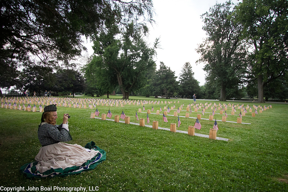 "Lisa Donnelly takes a moment in the shade to take a picture of the flags and luminaria set out at the Soldiers National Cemetery, during the Sesquicentennial Anniversary of the Battle of Gettysburg, Pennsylvania on Sunday, June 30, 2013.   Following ""A New Birth of Freedom"" program at Meade's Headquarters, a procession by candlelight was led to the cemetery. John Boal photography"