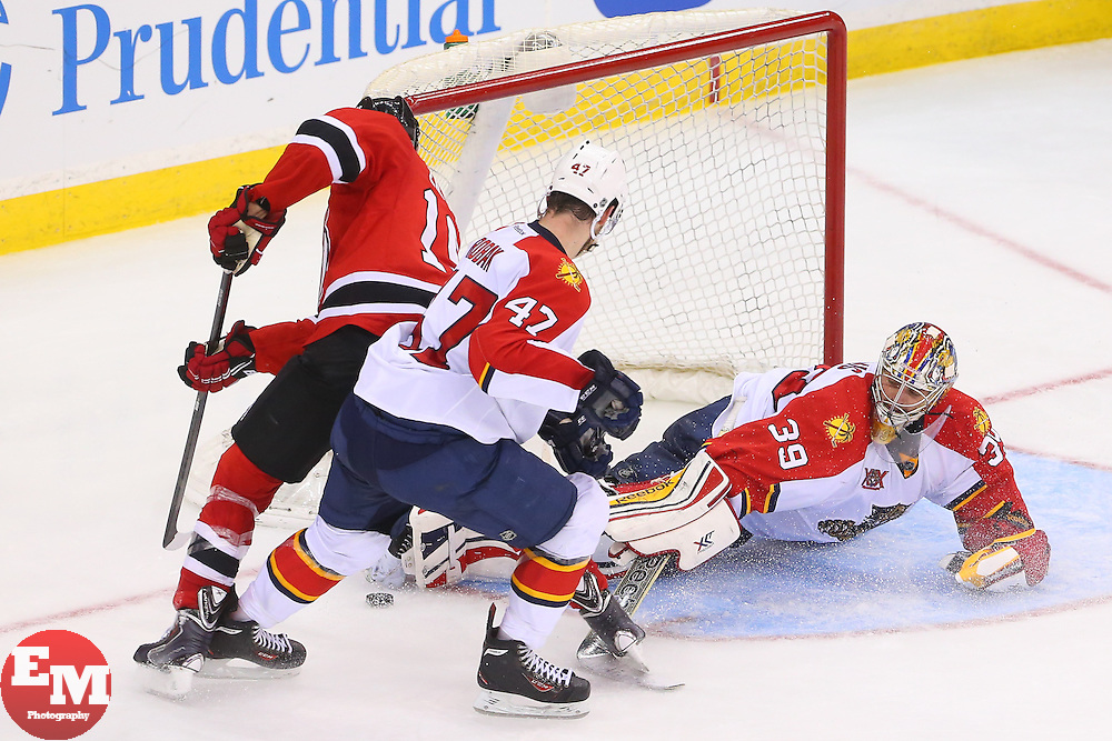 Mar 31, 2014; Newark, NJ, USA; Florida Panthers goalie Dan Ellis (39) makes a save on New Jersey Devils center Travis Zajac (19) during the third period at Prudential Center. The Devils defeated the Panthers 6-3.