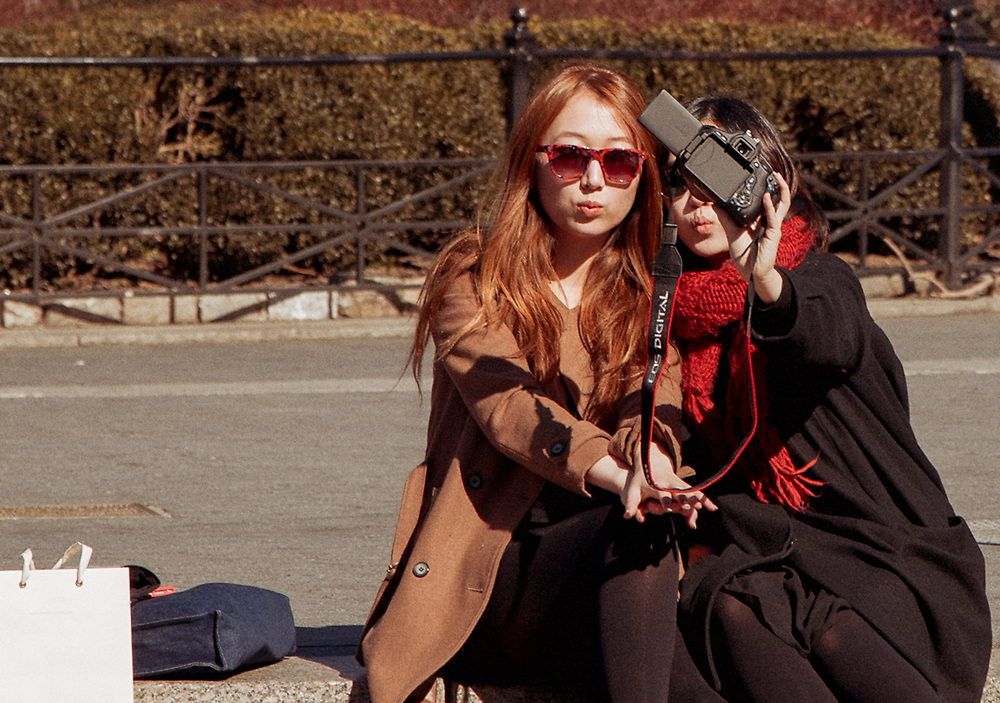 Two pretty Asian girls taking a selfie in Union Square. NYC 2012