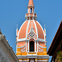 Belfry of Cathedral of Cartagena in Old Town, Cartagena, Colombia <br /> It is difficult – no impossible – to fully appreciate the salmon-colored bell tower and dome of the Cathedral of Cartagena from its front portal.  Yes, it is visible when walking along the city walls and from afar at Castillo San Felipe.  However, the best view to fully appreciate its elegance and beauty is by approaching the cathedral from a street called Calle San Pedro Claver.