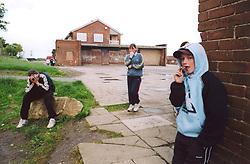 Teenage children hanging around outside youth club; run down council housing estate; Bradford UK