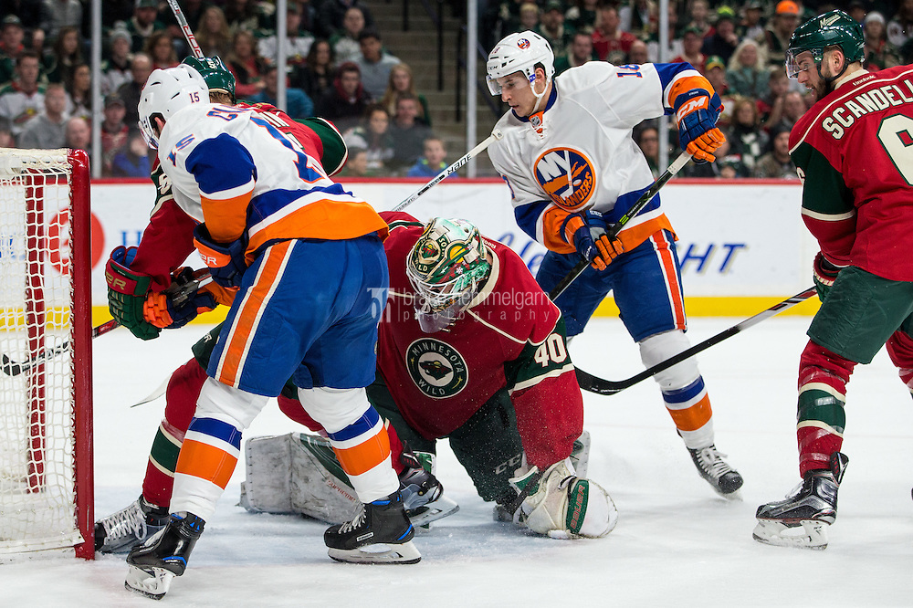 Dec 29, 2016; Saint Paul, MN, USA; Minnesota Wild goalie Devan Dubnyk (40) makes a save in front of New York Islanders forward Cal Clutterbuck (15) and forward Ryan Strome (18) during the first period at Xcel Energy Center. Mandatory Credit: Brace Hemmelgarn-USA TODAY Sports