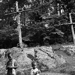 Kyle Green | The Roanoke Times<br /> June 13, 2009 - Pastor, Jerry Powell (right), takes a cell phone picture of a re-creation of the site of Jesus' crucifixion along with his son, Jerry Powell Jr. (middle, age 3), and Zahmel Wright (left, age 9) at Holy Land USA in Bedford, Virginia. Holy Land USA is a walking or motorized tour following key events in the life of Christ. Pastor Powell was taking the tour with a church group who traveled 3 1/2 hours from Emporia, Virginia.