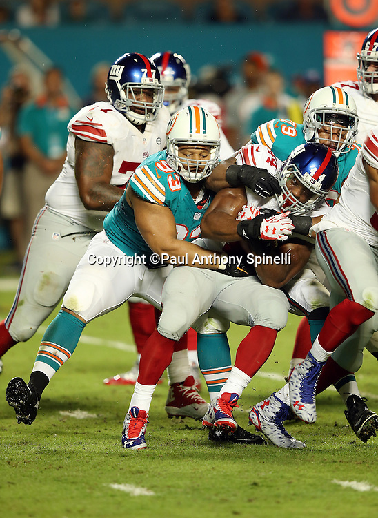New York Giants running back Andre Williams (44) gets gang tackled by Miami Dolphins defensive tackle Ndamukong Suh (93) and Miami Dolphins defensive end Derrick Shelby (79) as he runs the ball in the second quarter during the NFL week 14 regular season football game against the Miami Dolphins on Monday, Dec. 14, 2015 in Miami Gardens, Fla. The Giants won the game 31-24. (©Paul Anthony Spinelli)