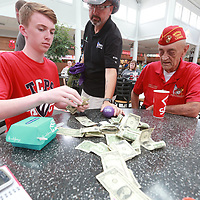 Scott Burns, center, looks in as volunteers begin to count how much he raised during a prize a give away Friday at The Mall at Brnes Crossing in Tupelo.