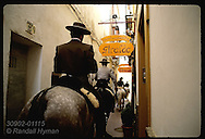 Horsemen in traditional attire ride Andalusian steeds down alley in Barrio de Santa Cruz; Seville Spain