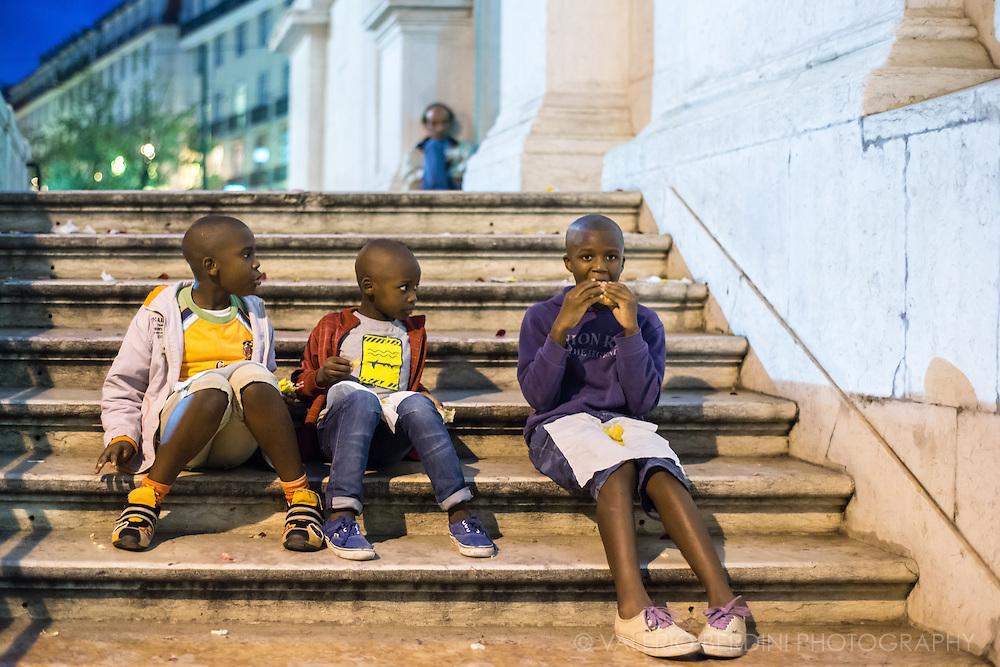 Three boys and a sandwich on the staircase of Igreja da Nossa Senhora de Encarnacao, a church in Barrio Alto.