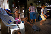 Solange Da Silva Correia prepares a meal inside her riverside home near the town of Caviana in Amazonas, Brazil while her grandchildren play with a turtle that they will eat for a special meal.    (Solange Da Silva Correira is featured in the book What I Eat: Around the World in 80 Diets.)  The caloric value of her day's worth of food on a typical day in the month of November was 3400.  She is 49 years of age; 5 feet 2.5 inches tall; and 168 pounds.