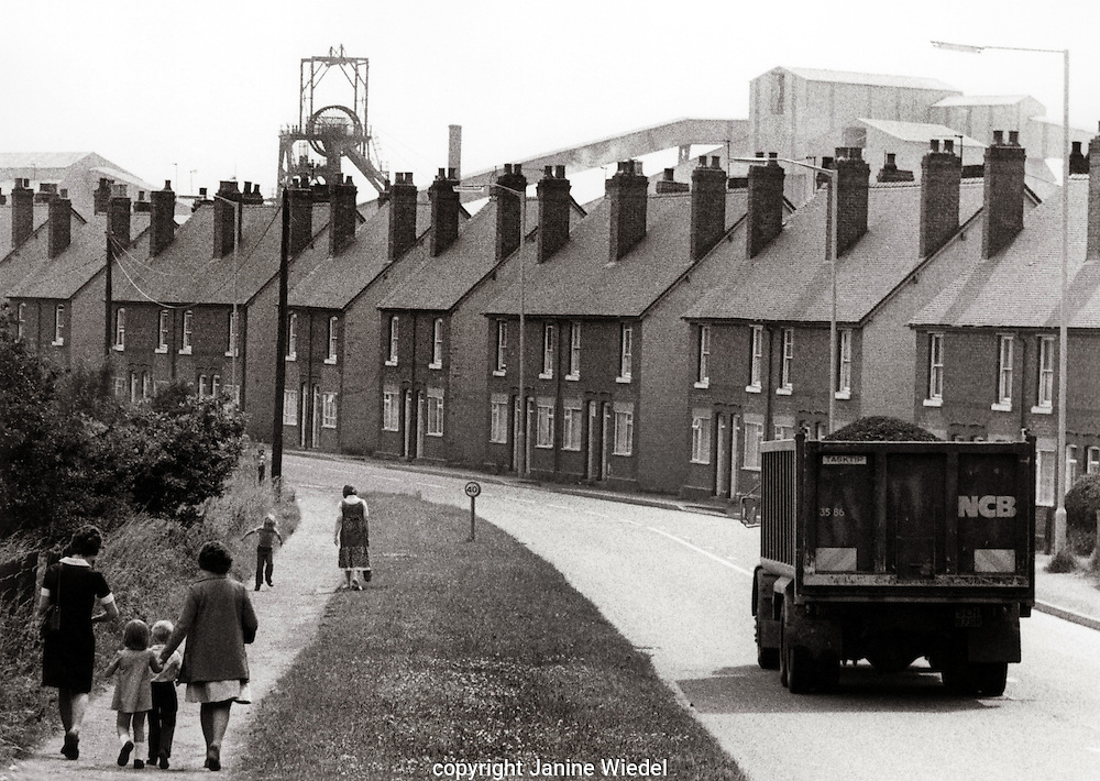 Row of workers cottages with coal mine looming behind.