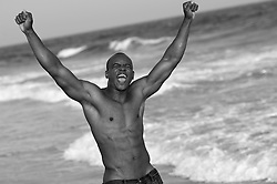 Young shirtless man expressing joy on the beach