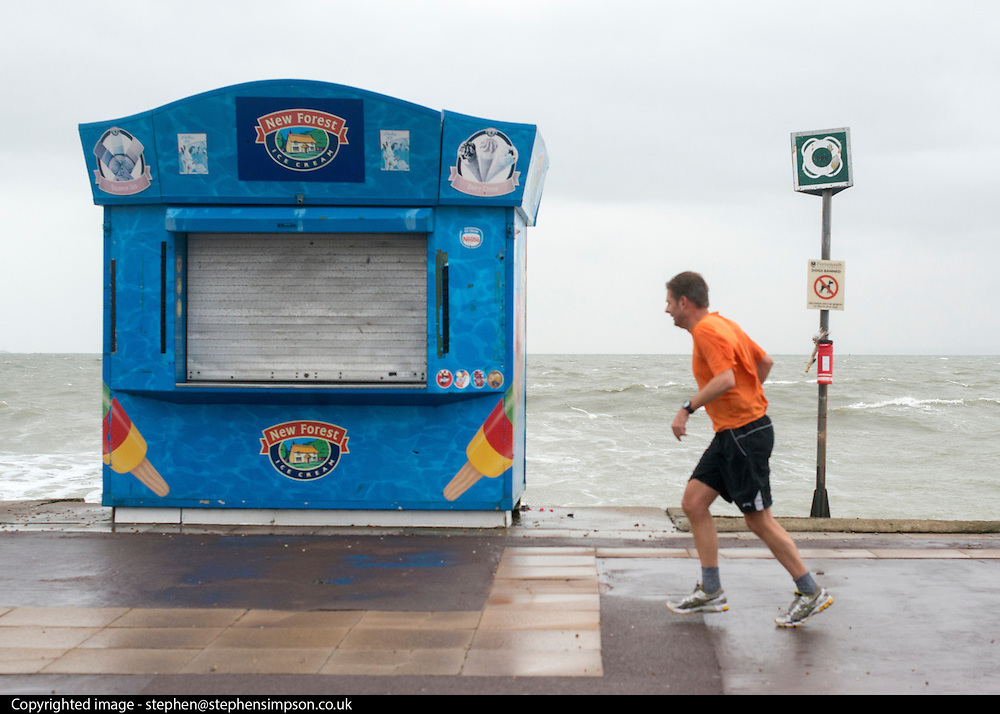 © Licensed to London News Pictures. 11/11/2014. Southsea, UK. A wet jogger passes a closed ice cream stall. Wet and windy weather today, 11 November 2014, at Southsea, Portsmouth. The Met Office have issued weather warnings in some parts of the UK. Photo credit : Stephen Simpson/LNP