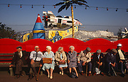 A daytrip of old age pensioners are seated on a bench in Great Yarmouth, a seaside resort in eastern England.