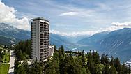 La tour de Vermala à Crans-Montana<br /> Architecture en montagne, Alpes Suisse, Valais.<br /> La fin des années 1950 voit l'apparition de la parahôtellerie, phénomène qui va considérablement changer l'aspect de la station. Celle-ci perd son image de lieu de cure, suite à la régression de la tuberculose, au profit de celle de station mondaine. C'est donc dans une période de boom économique que l'architecte Jean-Marie Ellenberger reçoit le mandat de construire une sep- tantaine d'appartements dans un lieu caractérisé par une végétation abondante. Confronté à cette problématique délicate, l'architecte y répond par une tour de 19 étages, dont la faible emprise au sol permet de préserver la forêt environnante. Le projet a été mal accueilli par la popula- tion. La construction de tours en montagne n'est pourtant pas une nou- veauté dans les années 1960, mais l'architecture adoptée est sans conces- sion face à l'image rassurante du «chalet suisse».<br /> La tour de Super-Crans, qui se distingue par une unité de conception et une unité des matériaux employés, est caractérisée par sa forme en éventail. Reprise de l'architecte Alvar Aalto, elle permet un ensoleillement maximal. A la tour s'ajoute un bâtiment bas de cinq étages qui lui est relié par un socle abritant le lobby, ainsi qu'une piscine. La façade rideau et les stores aux couleurs pures –rouge, bleu et jaune – rappellent la Cité Radieuse de Le Corbusier. Ce «phare», signé par un architecte réputé, aurait pu devenir la fierté de la station. Mais il n'a jamais était aussi décrié que quarante ans après sa construction.<br /> Mountain architecture, Swiss Alps, Valais.<br /> (OLIVIER MAIRE)