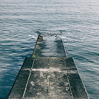 small concrete jetty at Lyme Regis beach with horizon and calm sea