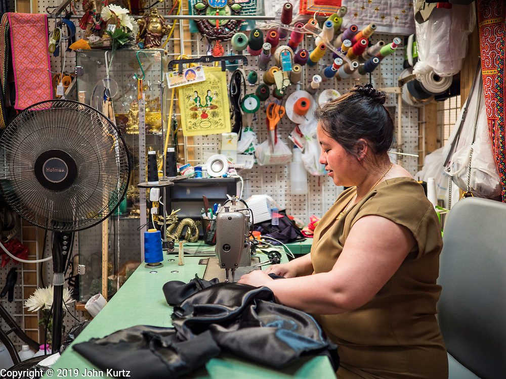 03 AUGUST 2019 - ST. PAUL, MINNESOTA: A woman sews clothes in her shop in the Hmongtown Marketplace. Thousands of Hmong people, originally from the mountains of central Laos, settled in the Twin Cities in the late 1970s and early 1980s. Most were refugees displaced by the American war in Southeast Asia. According to the 2010 U.S. Census, there are now 66,000 ethnic Hmong in the Minneapolis-St. Paul area, making it the largest urban Hmong population in the world. There are two large Hmong markers in St. Paul. The Hmongtown Marketplace has are more than 125 shops, 11 restaurants, and a farmers' market in the summer. Hmong Village is newer and has more than 250 shops and 17 restaurants.    PHOTO BY JACK KURTZ