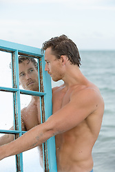 sexy man in the ocean looking at himself in a mirror