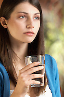 Young woman drinking glass of water portrait