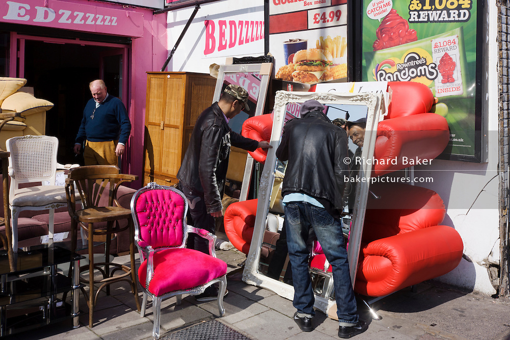 Buyers admire mirrors and their own reflections with bright furniture on sale in a London street.