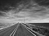 A loaded vehicle comes into view over a crest in the road with a contrail above in rural Klickitat County, WA, USA (monochrome high contrast grainy image)