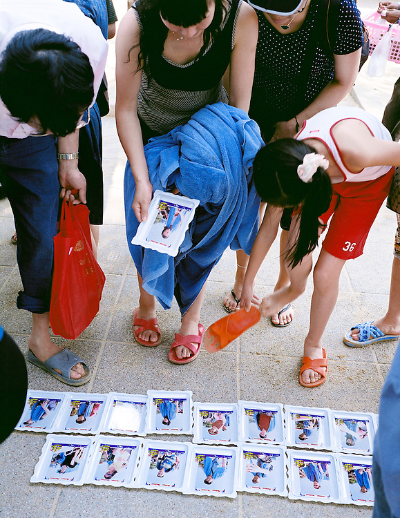 Tourists purchase photo-souvenirs of themselves on their boat trip on Pattaya Bay.