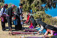 Puno, Peru - July 25, 2013: priest blessing women weaving in the peruvian Andes at Taquile Island on Puno Peru at july 25th, 2013.