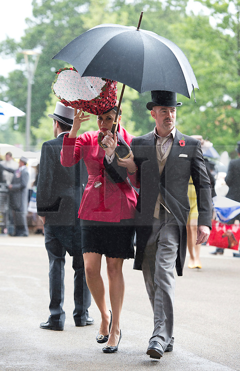 © London News Pictures. 22/06/2013. Ascot, UK.  Racegoers shelter from rain and strong winds on day 5 of Royal Ascot at Ascot racecourse in Berkshire, on June 20, 2013.  The 5 day showcase event,  which is one of the highlights of the racing calendar, has been held at the famous Berkshire course since 1711. Photo credit should read: Ben Cawthra/LNP