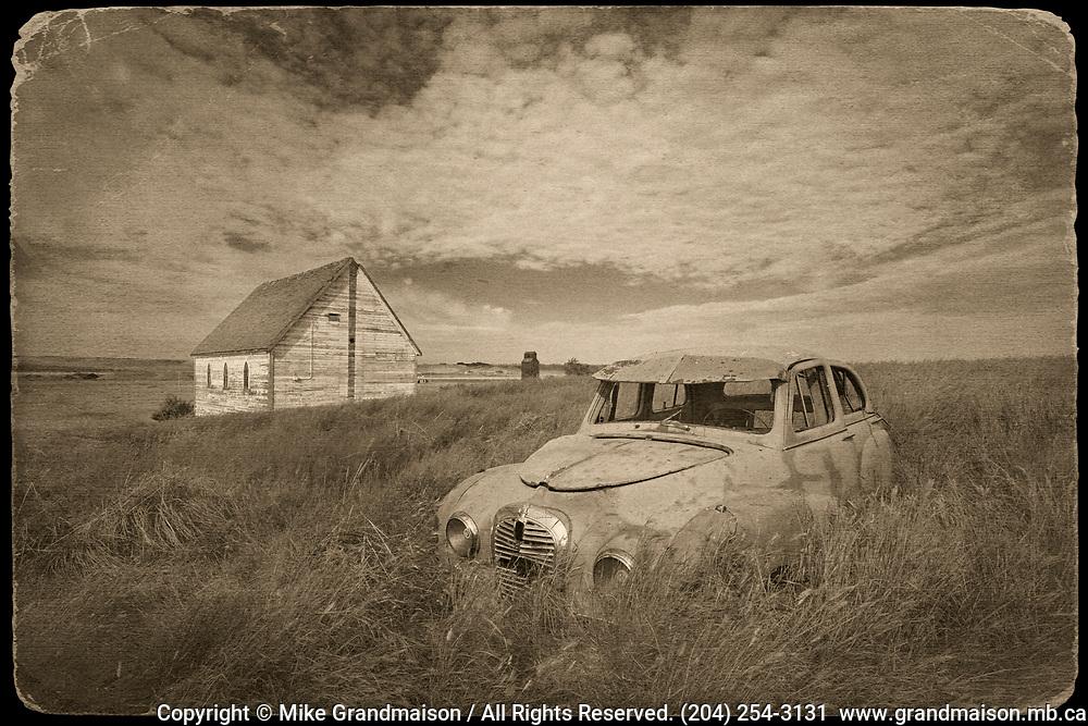 Abandoned car and church in prairie ghost town<br /> Neidpath<br /> Saskatchewan<br /> Canada