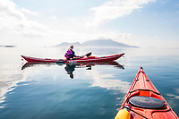 A portrait of a woman in her sea kayak off the southe east shore of Orcas Island near Doe Bay, Rosario Strait, with Cypress Island in the background, Washington State, USA.