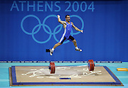 Picture taken at the Nikaia Olympic Weightlifting Hall at the 2004 Athens Olympic Games.  The Finals of the Mens 85kg Snatch and Clean and Jerk. Pic shows Greek Lifter Pyrros Dimas, who had won three previous gold medals, leaps in the air after a lift during the Mens 85kg Snatch and Clean and Jerk.. He finished with the Bronze medal. <br /> Commissioned by Fairfax Media