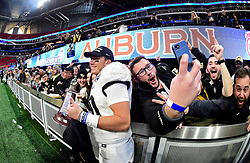 Fans swarm UCF Knights quarterback McKenzie Milton (10) after the Chick-fil-A Peach Bowl NCAA college football game against Auburn University at the Mercedes-Benz Stadium in Atlanta, January 1, 2018. UCF won 34-27 to go undefeated for the season. (David Tulis via Abell Images for Chick-fil-A Peach Bowl)