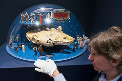 "© Licensed to London News Pictures. 06/12/2019. LONDON, UK. A staff member poses with a  ""The Empire Strikes Back, Toy Figures And Millennium Falcon Toy Shop Display"", British, c. 1980, (Estimate GBP7,000-10,000), at the preview of ""Star Wars Online"", a sale dedicated to Star Wars collectibles encompassing 100 lots from the franchise.  Sotheby's will host the online-only sale which will run until 13 December, ahead of the final film in the sequel trilogy ""Star Wars: The Rise of Skywalker"".  Highlights from the sale are on display at Sotheby's New Bond Street 6 to 11 December.  Photo credit: Stephen Chung/LNP"