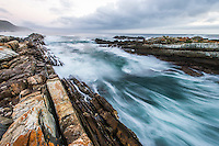 Waves push through a narrow rocky channel in the Tsitsikamma Marine Protected Area. Eastern Cape. South Africa