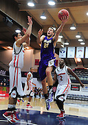November 28, 2011; Moraga, CA, USA; San Francisco State Gators forward Griffin Reilly (21) drives to the basket against Jacksonville State Gamecocks forward Rinaldo Mafra (left) during the first half of the Shamrock Office Solutions Classic consolation game at McKeon Pavilion.