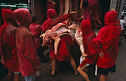 A group of red uniformed meat market traders manhandle joints of pork from the back of a meat wagon at Macau's main meat market, on the Rua Sul do Mercado de Sao Domingos, just off the Avenida de Almeida Ribeiro, in Central Macau.