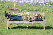 © Licensed to London News Pictures. 11/03/2015. Kew, UK. A woman rests on a bench in the warm sunshine. People enjoy the cross displays at Kew Garden's today 11th March 2015. The display features the variety Crocus tommasinianus. The Uk has enjoyed warm sunny weather this week.  Photo credit : Stephen Simpson/LNP