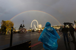 © Licensed to London News Pictures. 10/11/2014. London, UK. A tourist in a rain poncho looks at a rainbow over the London Eye during rain near Westminster Bridge in central London this afternoon. Photo credit : Vickie Flores/LNP