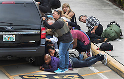 January 6, 2017 - Fort Lauderdale, Florida, U.S. - People take cover at the Ft. Lauderdale Airport after a gunman killed 5 people and injured many more. A gunman killed five people and injured eight Friday at Fort Lauderdale-Hollywood International Airport, which was forced to shut down and thrust into chaos. The suspect was identified as Esteban Santiago. (Credit Image: © Allen Eyestone/The Palm Beach Post via ZUMA Wire)
