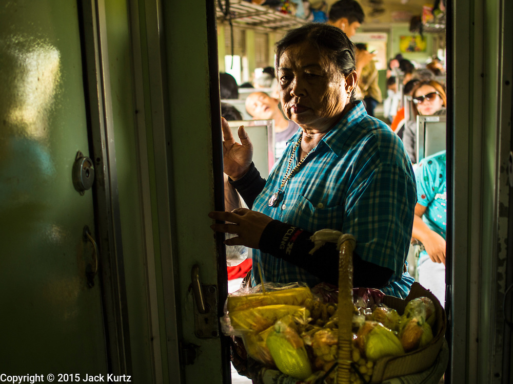 19 MARCH 2015 - AYUTTHAYA, AYUTTHAYA, THAILAND:   A fruit vendor works the Ayutthaya to Bangkok third class train. The train line from Bangkok to Ayutthaya was the first rail built in Thailand and was opened in 1892. The State Railways of Thailand (SRT), established in 1890, operates 4,043 kilometers of meter gauge track that reaches most parts of Thailand. Much of the track and many of the trains are poorly maintained and trains frequently run late. Accidents and mishaps are also commonplace. Successive governments, including the current military government, have promised to upgrade rail services. The military government has signed contracts with China to upgrade rail lines and bring high speed rail to Thailand. Japan has also expressed an interest in working on the Thai train system. Third class train travel is very inexpensive. Many lines are free for Thai citizens and even lines that aren't free are only a few Baht. Many third class tickets are under the equivalent of a dollar. Third class cars are not air-conditioned.   PHOTO BY JACK KURTZ