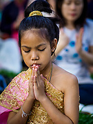 "17 MARCH 2018 - BANGKOK, THAILAND:  A girl in traditional Thai clothes prays during a ""sticky rice merit making"" in Lumpini Park in Bangkok. Sticky rice merit making is a merit making in the Isan / Lao style, when people present small amounts of cooked sticky rice (also known as glutinous rice) to Buddhist monks. Isan is the northeast region of Thailand.     PHOTO BY JACK KURTZ"