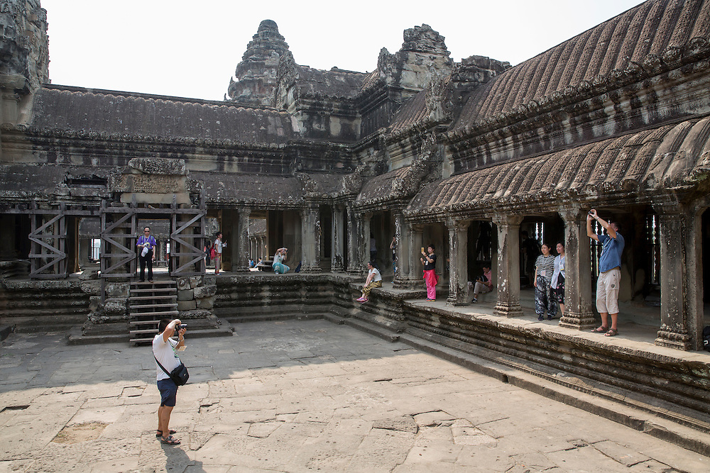 Tourists explore and photograph within one of the galleries in the ancient temple complex of Angkor Wat, Siem Reap, Cambodia.  Angkor Wat is one of UNESCO's world heritage sites. It was built in the 12th century and covers 162 hectares.  It is Cambodia's main tourist attraction.  (photo by Andrew Aitchison / In pictures via Getty Images)