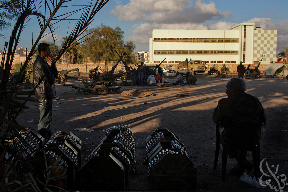 Libyan opposition volunteers sit near several refurbished anti-aircraft weapons and multiple cans of prepared ammunition February 28, 2011 at a volunteer military camp in the eastern Libyan city of Benghazi. Opposition forces are on guard for airstrikes by forces of Libyan leader Col Muammar el-Qaddafi across eastern Libya after a reported airstrike on an opposition weapons deport near the city of Ajdabia. .Slug: Libya.Credit: Scott Nelson for the New York Times