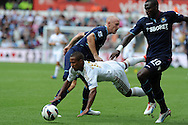 Swansea city's Wayne Routledge © is sent flying by West Ham's James Collins (l) and Guy Demel ®. . Barclays Premier league, Swansea city  v West Ham Utd at the Liberty Stadium in Swansea, South Wales  on Saturday 25th August 2012. pic by Andrew Orchard, Andrew Orchard sports photography,