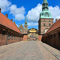 Southern Entrance to to Frederiksborg Castle in Hiller&oslash;d, Denmark <br /> The southern entrance to Frederiksborg Castle builds anticipation with every step. First you walk across a bridge and through the Town Gate. This cobblestone street named Staldgaden brings you passed the Hussar Stables on the right and the Royal or King&rsquo;s Stables on the left.  Directly ahead is one of two Frederik II&rsquo;s Round Towers and the Christian VI&rsquo;s Gateway which is dated 1736. Next is the S-bridge that leads to the Gatehouse. You have arrived!  Now stop to marvel at the spectacular main castle that stands before you on the middle islet.