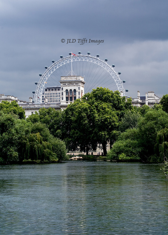 View from St. James Park lake toward the London Eye and Foreign  Commonwealth Office, Union Jack flag flying from its square tower.  A heavy cluster of summer green trees in full leaf extends across the image separating lake water from the architecture and wheel beyond.