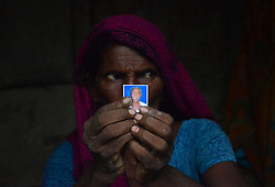 July 10, 2017 - Chandmati, India - A woman holds a photograph of her husband, who died after consuming poisonous alcohol, inside her temporary shelter during rains, in the Indian village of Kewatiya. At least 18 people have died consuming poisonous alcohol, according to Indian officials. (Credit Image: © Ritesh Shukla/NurPhoto via ZUMA Press)
